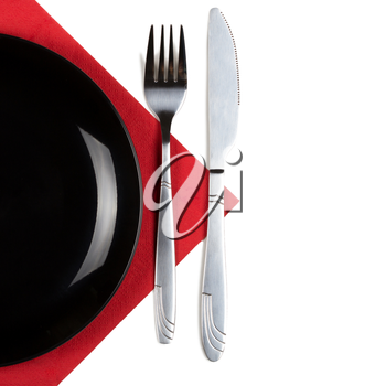 Black plate, fork and knife on red napkin. Isolated on white. Square format.