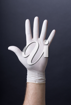 Male palm in latex glove. Doctor or nurse hand in sanitary glove. Dark background