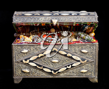 ancient east treasure chest with antique jewelry isolated on black background