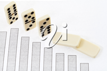 business concept - fallen domino and graph of decline economy results