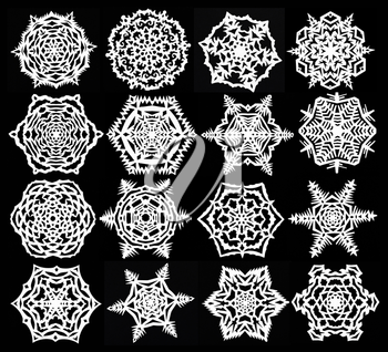 set of hand made cut out white snowflakes on black paper background