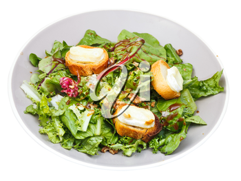 green salad with goat cheese and toasted bread on plate isolated on white background