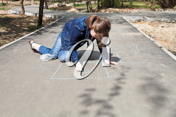 girl drawing hopscotch outdoors in sunny day