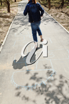 girl hopping in hopscotch on urban alley in sunny day