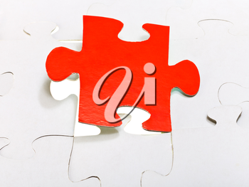 red puzzle piece attached in layer of assembled puzzles
