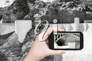 travel concept - tourist shooting photo of Hoover Dam on mobile gadget, USA