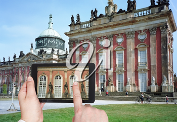 travel concept - tourist taking photo of statues of New Palace in Sanssouci Royal Park, Potsdam on mobile gadget, Germany
