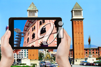 travel concept - tourist takes picture of bullring Arena de Barcelona on Placa Espanya, Barcelona on smartphone,