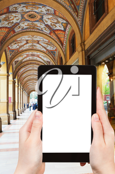 travel concept - tourist photograph medieval artistic portico on piazza Cavour in Bologna, Italy on tablet pc with cut out screen with blank place for advertising logo