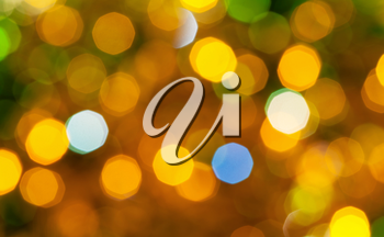 abstract blurred background - brown and green shimmering Christmas lights bokeh of electric garlands on Xmas tree