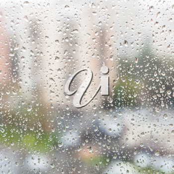 rainy weather in city - view of rain drops on window glass of apartment house