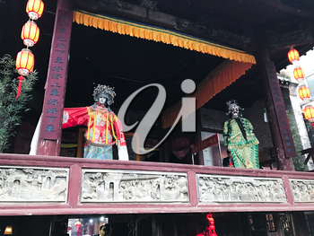 XINGPING, CHINA - MARCH 30, 2017: puppets on facade of ancient opera stage in Xing Ping town in Yangshuo county. The town was settled in 265 AD, Xingping is surrounded by great examples of Karst peaks