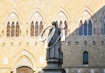 travel to Italy - statue of medieval Italian archdeacon Sallustio Bandini on Piazza Salimbeni and wall of Gothic style Palazzo Salimbeni in Siena city in winter