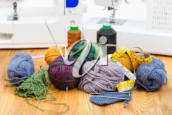 needlework still life - knitting materials, threads on table and sewing machines on background