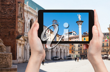 travel concept - tourist photographs monuments on Piazza dei Signori in Vicenza city in Italy on tablet