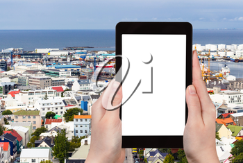 travel concept - tourist photographs harbor in Reykjavik city in Iceland in september on tablet with cut out screen for advertising logo