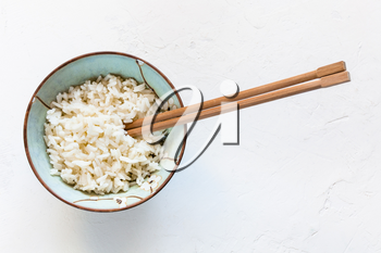 top view of chopsticks in bowl with boiled rice on white concrete board