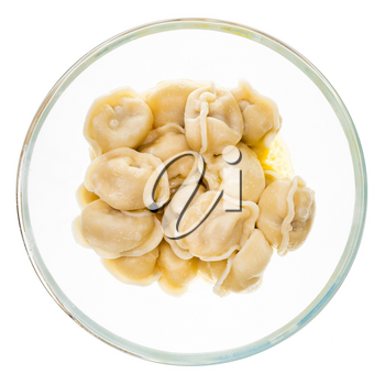 top view of buttered Pelmeni (russian dumplings filled with minced meat) in glass bowl isolated on white background