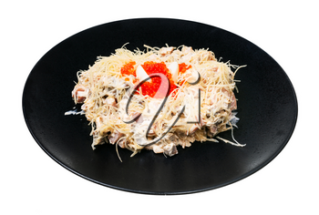 served Quail Nest salad from ham, veal and beef tongue, grated cheese, dressed with mayonnaise and decorated by quail egg and salmon caviar on black plate isolated on white background