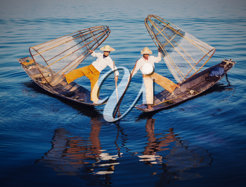 Myanmar travel attraction - Traditional Burmese fishermen balancing with fishing nets at Inle lake in Myanmar. Vintage filtered retro effect hipster style image