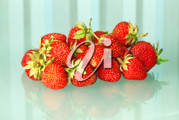 Heap of red fresh strawberries on a transparent blue striped background.