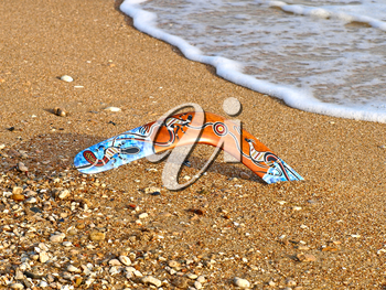 Colorful boomerang on a sandy beach.