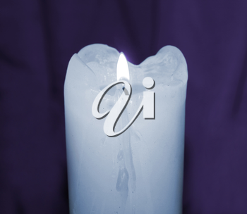 Glowing mourning candle in darkness taken closeup on purple.