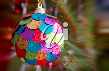 Multicolored Christmas ball on pine branch taken closeup with soft bokeh.
