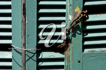 light green wood venetian blind and a rusty chain in la boca buenos aires argentina