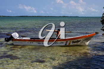 a man and his white boat in the lagoon of sian kaan mexico