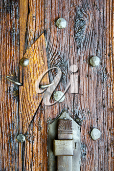 in  italy  patch lombardy    cross castellanza blur   abstract   rusty brass brown knocker  a  door curch  closed wood