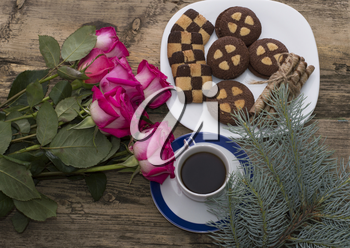 bouquet of beautiful roses, coniferous branch, cookies and coffee, a festive card on a subject flowers