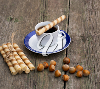coffee, baking in the form of tubules and nutlets, on a wooden table, a subject of sweet and drinks