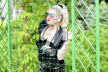 the beautiful woman at an iron wire fence, a subject beautiful women