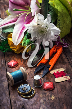 sewing accessories with a bouquet of fresh flowers.the image is tinted in vintage style