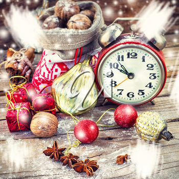An alarm clock and bag of nuts on the background of Christmas decorations