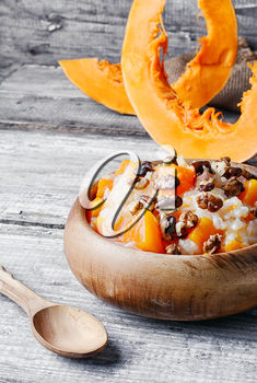 Porridge with pumpkin in a stylish wooden bowl, rustic