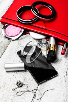 Fashionable ladies handbag with cosmetics and phone on light background