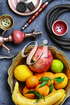 Eastern smoking hookah and dish with tangerines,pomegranate and lime