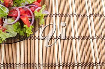Background for food styling of a transparent plate of fresh vegetarian salad of raw vegetables and bamboo mat