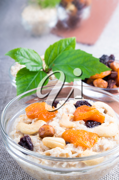 One portion of oatmeal with fruit and berries in a glass bowl for breakfast with a blurred background