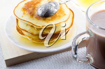 Glass mug of hot cocoa and pancakes with honey close-up with shallow depth of field