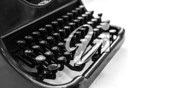 Old manual typewriter machine, closeup fragment with keyboard over white background, black and white photo with soft selective focus