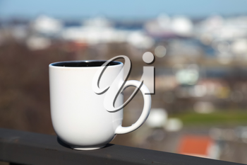 White cup of coffee stands on balcony railing above blurred cityscape