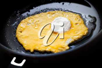 Original roasted eggs with white center and yellow base in black pan