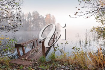 Small wooden pier on still lake in autumn foggy morning