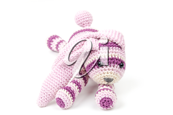 Knitted pink rabbit toy lays isolated on white background, selective focus with shallow DOF