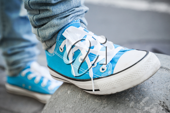 Brand new blue shoes, urban walking theme. Closeup photo with selective focus and shallow DOF