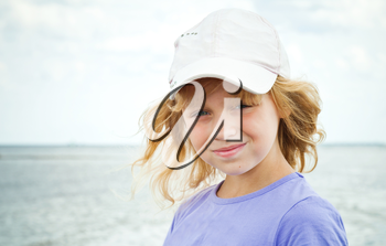 Portrait of a slightly smiling little blond beautiful Russian girl on the sea coast
