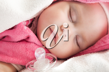 Baby girl sleeps in pink and white cotton towels with a pacifier nearby;